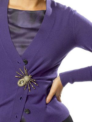antique jewelry on a cardigan